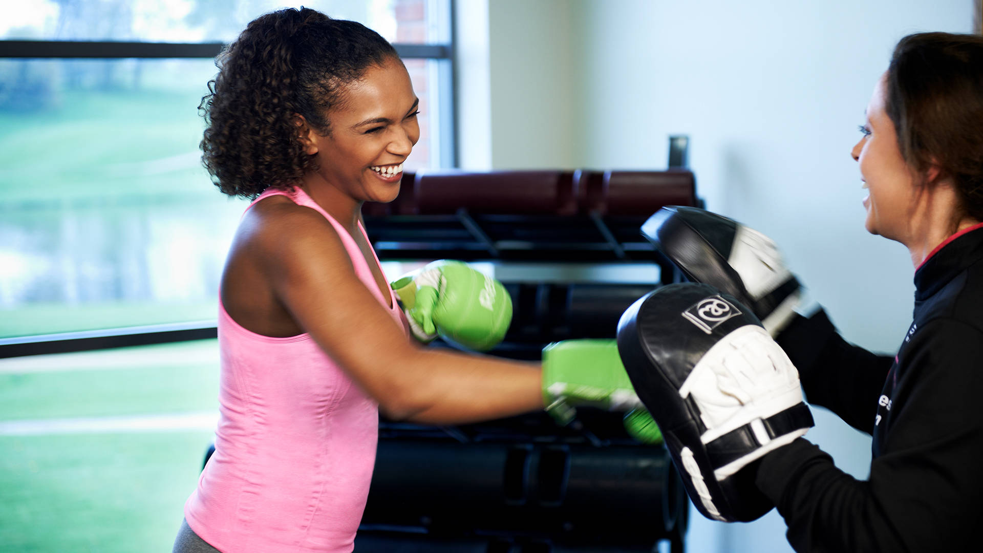 A female health club member and female personal training using boxing gloves and pads
